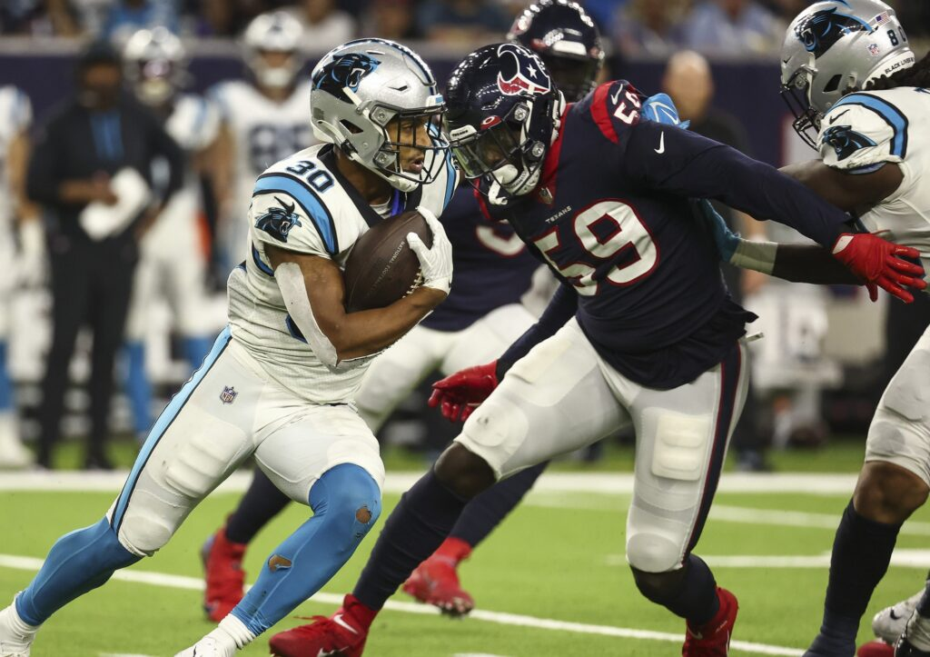 Sep 23, 2021; Houston, Texas, USA; Carolina Panthers running back Chuba Hubbard (30) runs with the ball as Houston Texans defensive end Whitney Mercilus (59) attempts to make a tackle during the fourth quarter at NRG Stadium. Mandatory Credit: Troy Taormina-USA TODAY Sports
