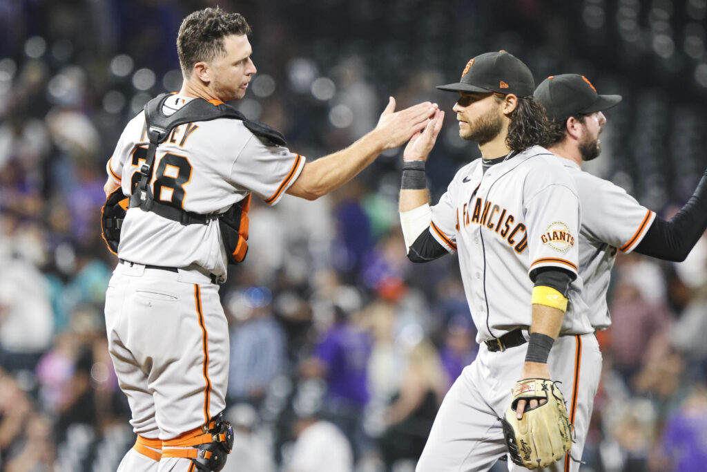 Sep 25, 2021; Denver, Colorado, USA; San Francisco Giants catcher Buster Posey high fives shortstop Brandon Crawford after beating the Colorado Rockies 7-2 at Coors Field. Mandatory Credit: Michael Ciaglo-USA TODAY Sports