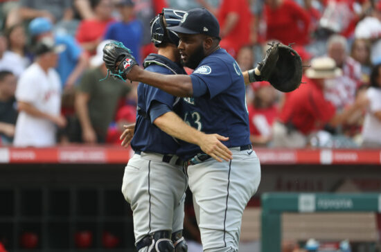 Sep 26, 2021; Anaheim, California, USA; Seattle Mariners pitcher Diego Castillo (63) and catcher Tom Murphy (2) celebrates a win against the Los Angeles Angels at Angel Stadium. The Mariners won 5-1. Mandatory Credit: Kiyoshi Mio-USA TODAY Sports