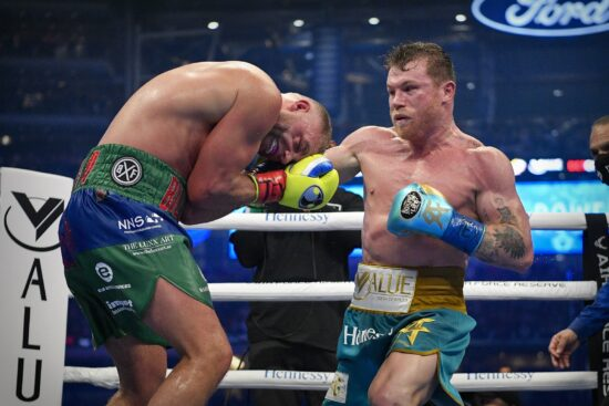 May 8, 2021; Arlington, Texas, USA; Canelo Alvarez (teal trunks) and Billy Joe Saunders (blue green trunks) during a super middleweight boxing title fight at AT&T Stadium. Mandatory Credit: Jerome Miron-USA TODAY Sports