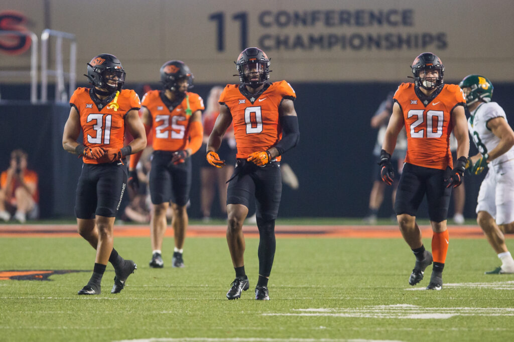 Oct 2, 2021; Stillwater, Oklahoma, USA;  Oklahoma State Cowboys safety Kolby Harvell-Peel (31) and cornerback Christian Holmes (0) and linebacker Malcolm Rodriguez (20) walk back to the huddle after a play during the fourth quarter against the Baylor Bears at Boone Pickens Stadium. OSU won 24-14. Mandatory Credit: Brett Rojo-USA TODAY Sports