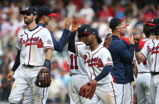 Oct 11, 2021; Cumberland, GA, USA; Atlanta Braves second baseman Ozzie Albies (middle) celebrates with teammates after defeating the Milwaukee Brewers during game three of the 2021 ALDS at Truist Park. Mandatory Credit: Brett Davis-USA TODAY Sports