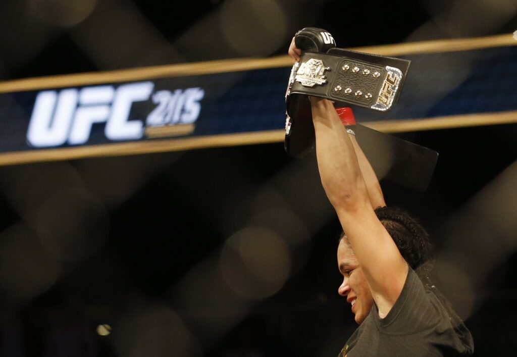 Sep 9, 2017; Edmonton, Alberta, Canada;  Amanda Nunes (red gloves) celebrates with the championship belt after defeating Valentina Shevchenko (blue gloves) during UFC 215 at Rogers Place. Mandatory Credit: Perry Nelson-USA TODAY Sports