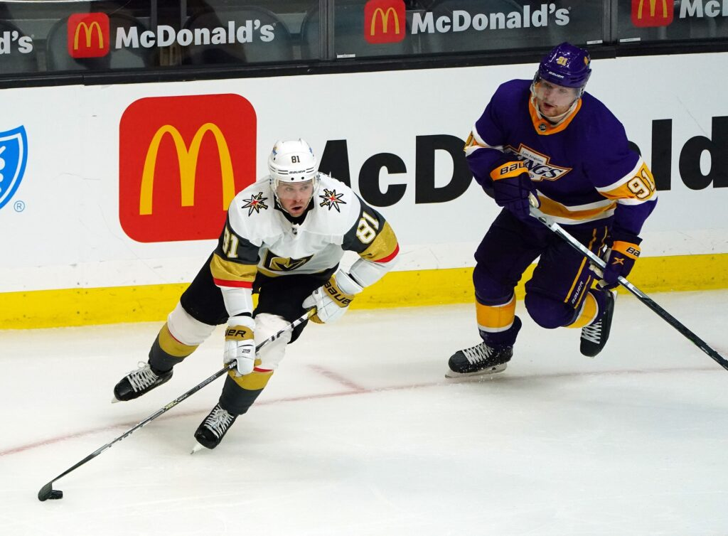 Apr 14, 2021; Los Angeles, California, USA; Vegas Golden Knights center Jonathan Marchessault (81) moves the puck ahead of Los Angeles Kings left wing Carl Grundstrom (91) during the third period at Staples Center. Mandatory Credit: Gary A. Vasquez-USA TODAY Sports